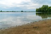 Sandy Shore Of The Lake With A Quiet Surface Of Water Under A Cloudy Overcast Sky poster