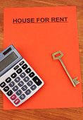 Advertise rental houses on red paper on wooden background