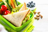 School Lunch Box With Sandwich, Vegetables, Banana, Yogurt, Nuts And Berries On White Wooden Table.  poster