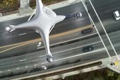 Unmanned Aircraft System Quadcopter Drone In The Air Over Roadway with Automobiles. poster