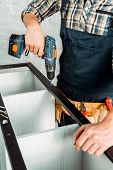 Cropped View Of Installer Holding Hammer Drill While Installing Rack poster