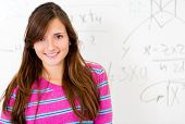 Beautiful female student smiling with a whiteboard at the background