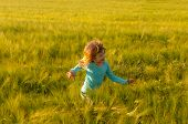 Cute happy girl running in the field of wheat on sunny spring day