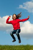Cute teenage girl jumping with joy on sunny spring day