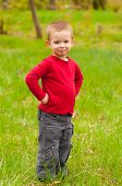 Cute smiling little boy standing in the middle of the meadow on beautiful spring day
