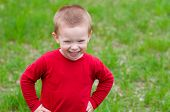 Cute little boy with beautiful smile plays in the grass