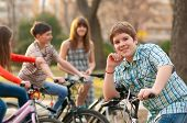 Four happy teenage friends riding bicycles in the park