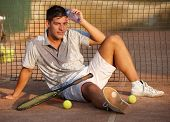 Handsome tennis player sitting on hard court, exhausted, looking at camera.