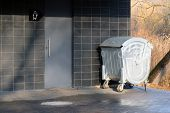 Entrance To The Public Toilet In The City Park And A Metal Litter Bin. The Door To The Building And  poster