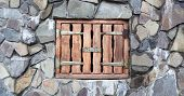Small Wooden Loading Door In Wall Of Old Stone Barn. Ancient Stone Wall With Small Strong Wooden Doo poster