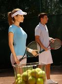 Young tennis players playing mixed doubles on tennis court.