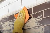 picture of grout  - Contractor grouting ceramic tiles on a wall - JPG