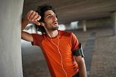 Portrait Of A Fitness Athlete Man In Earphone Breathing Heavily After Running And Doing Exercise - E poster