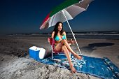 Young Brunette Woman sitting on chair at beach