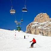 Skier going down the slope under ski lift at Sella Ronda ski route in Italy