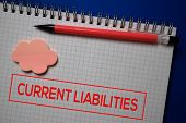 Current Liabilities Write On A Book Isolated On Blue Background. poster
