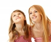 portrait of two sisters happy smiling (child and teen) looking up to corner, isolated on white background