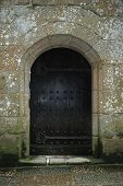 Ancient Wooden Entrance Bound With Metal In Stone Medieval Wall