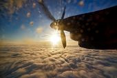 Airplane Engine And Propeller Over Clouds With Sun And Blue Sky poster