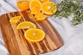 Fresh Orange Fruits Slices On Wooden Cutting Board. Juicy Orange Slices With Leaves. Tasty Organic F poster