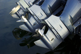 foto of outboard engine  - Three outboard boat motors against blue ocean - JPG
