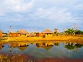 Bamboo Cottages And And Thier Reflections In Pond In Nakorn Ratchasima,thailand