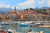 Colorful houses, church and marina with yachts and boats in Menton - town on French Riviera in Franc