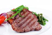 grilled meat beef steaks strips on white plate with sweet pea and tomatoes isolated over white backg