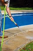 Hosing path around swimming pool.