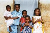 stock photo of overpopulation  - Real candid family photo of five cute and sweet black African sisters or girls all smiling in their sunday dress perfect for developing country and third world population issues.