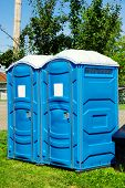 foto of porta-potties  - Two portable toilet or loo in blue plastic at a park public event or concert with white sign on door ready for text - JPG