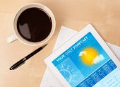 Workplace with tablet pc showing weather forecast and a cup of coffee on a wooden work table close-u
