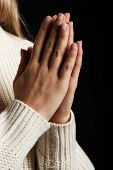 Young woman's praying. Close up on hands. On black background.
