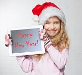Child in christmas hat with tablet pc. Happy girl showing tablet screen