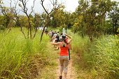 Girl Balances Water On Head While Hiking With Tourist Group Through The Jungle