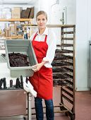 Portrait of female worker showing beef jerky in basket while standing at butcher's shop