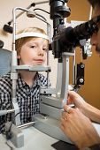 Portrait of preadolescent boy having his eyes tested with slit lamp by doctor