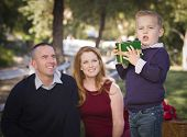 Handsome Young Boy Holding a Christmas Gift in the Park While His Mom and Dad Look On.