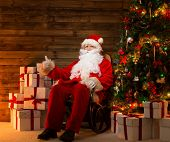Santa Claus sitting on rocking chair with thumb up in wooden home interior with gift boxes around hi