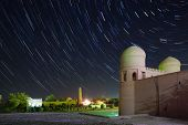 Western gate (Ata Darvoza) to ancient town of Itchan Kala at night with star trails. The city of Khi