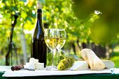 stock photo of baguette  - Two glasses of white wine bottle cheese and baguette - JPG