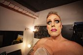 picture of cross-dressing  - Serious male in drag waiting in dressing room - JPG