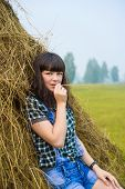 stock photo of hayfield  - Portrait of pretty brunette lying on haystack in summer hayfield - JPG