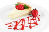 Slice of cheesecake with  strawberry and sauce on plate, isolated on white