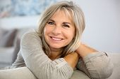 stock photo of sofa  - Smiling senior woman sitting in couch at home - JPG