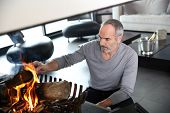 Mature man in modern house preparing fire