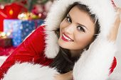 foto of flirtatious  - Portrait of pretty young woman dressed in Santa Claus outfit with hood smiling at the camera while lying on the ground - JPG