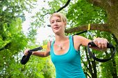 Young woman exercising with suspension trainer sling in City Park under summer trees for sport fitne