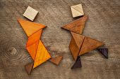 a couple of dancers or martial artists - abstract figures  built from tangram wooden pieces, a tradi