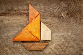 abstract picture of a sailing boat built from seven tangram wooden pieces over a rustic  barn wood,